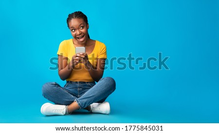 Positive African American Girl Using Smartphone Browsing Internet Sitting Over Blue Studio Background. Mobile App. Panorama, Empty Space Royalty-Free Stock Photo #1775845031