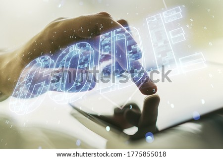 Creative Code word hologram and finger clicks on a digital tablet on background, artificial intelligence and neural networks concept. Multiexposure #1775855018