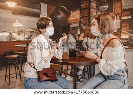 Friends girls met in a cafe and communicate with each other and chat. Wear medical protective masks. An outbreak of the coronavirus epidemic. New rules for social distance and isolation #1775860886