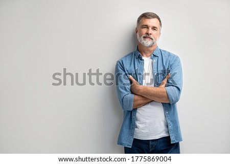 Portrait of smiling mature man standing on white background. Royalty-Free Stock Photo #1775869004