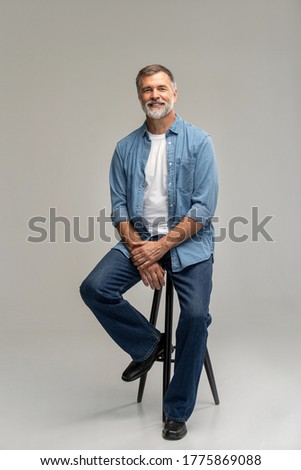 Portrait of a casual senior sitting on a chair on white background. Royalty-Free Stock Photo #1775869088