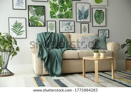 Beautiful artworks and comfortable couch in stylish room. Interior design Royalty-Free Stock Photo #1775884283