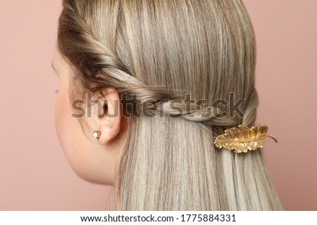 Young woman with beautiful gold hair clip on pink background, closeup Royalty-Free Stock Photo #1775884331