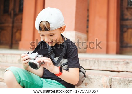 Boy with a digital camera taking pictures. School project for kids. Future profession. Summer holidays, memories and impressions. Club of photographers. Little boy wants to be a photographer.