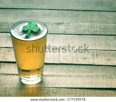 St. Patricks Day green shamrock floating in a cold, frosty glass of beer on a rustic wood background with room or space for copy, text, words.  Vintage camera instagram treatment for mood effect.
