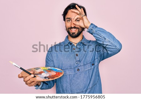 Young handsome hispanic artist man with bear holding painter palette and paintbrush with happy face smiling doing ok sign with hand on eye looking through fingers