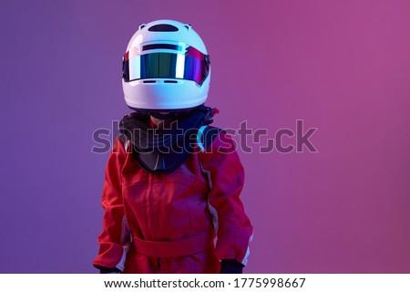 Cool boy child racer in helmet, racing suit, standing in neon light. Kart racing school poster. Competition announcement Royalty-Free Stock Photo #1775998667
