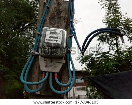 The electricity meter is installed on the electricity pole in rural villages for use in home appliances.