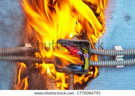 Electric fire caused by a short circuit in home electrical network. Damaged wiring caused overload of power system in house. Burned insulation of the electrical wires. The junction box ignited. Royalty-Free Stock Photo #1776086795