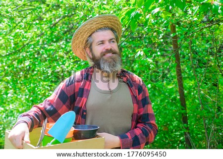 Happy bearded man in garden. Garden tools. Gardening. Eco-farm. Work in garden. Bearded man with gardening tools. Attractive man working in garden. Professional gardener. Gardener work. #1776095450