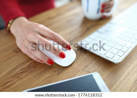 Close-up of person working on computer. Woman with red nails holding mouse for work. White keyboard on wooden desktop. Mobile phone on table. Business and career concept