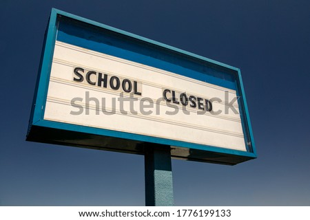 White sign with blue trim  against blue sky stating School Closed