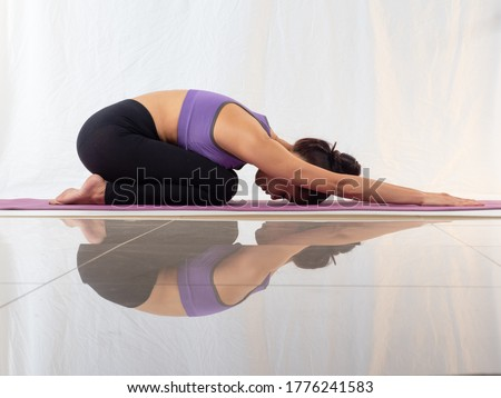 Healthy Asian woman wearing sportswear practicing yoga, Child's pose on white background wiht reflection on the floor. Royalty-Free Stock Photo #1776241583
