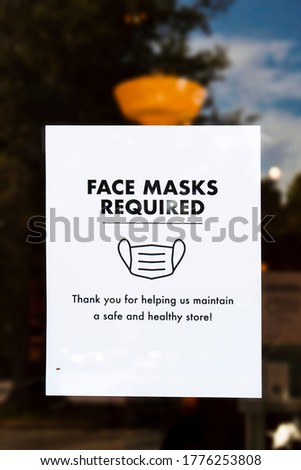Face Mask Required sign on door of store with reflection of sky and trees around it and bug crawling on it