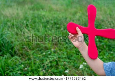 Child throwing four blade boomerang. Royalty-Free Stock Photo #1776293462