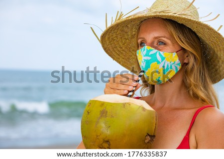 Funny portrait of woman in straw hat drinking young coconut on tropical sea beach. New rules to wear cloth face covering mask at public places due coronavirus COVID 19. Family holiday, summer travel