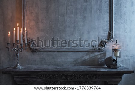 Mystical Halloween still-life background. Skull, candlestick with candles, old fireplace. Horror and witchery. Royalty-Free Stock Photo #1776339764