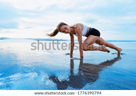 Sporty woman doing mountain climber exercise - run in plank to burn fat. Sunset beach, blue sky background. Healthy lifestyle at tropical island yoga retreat, outdoor activity, family summer vacation. #1776390794