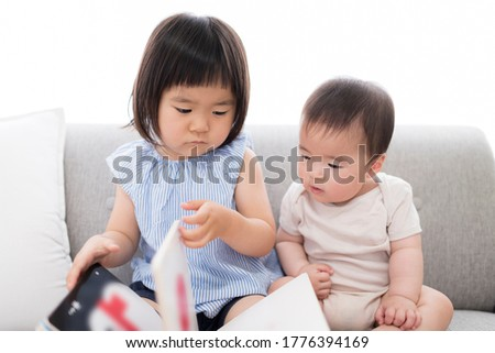 Young sisters reading picture books