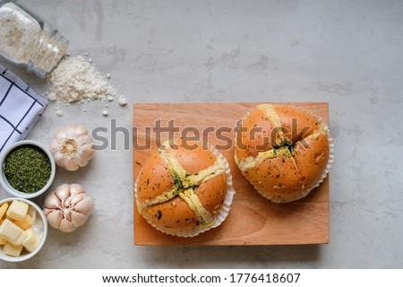 Top view, selective focus of Korean Garlic Cheese Bread (Yugjjog Maneulppang) made from bread bun, cream cheese, garlic, parsley and honey served on wooden board.  #1776418607