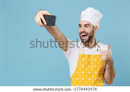 Excited young bearded male chef or cook baker man in apron white t-shirt toque chefs hat isolated on blue background studio. Cooking food concept. Doing selfie shot on mobile phone, showing thumb up
