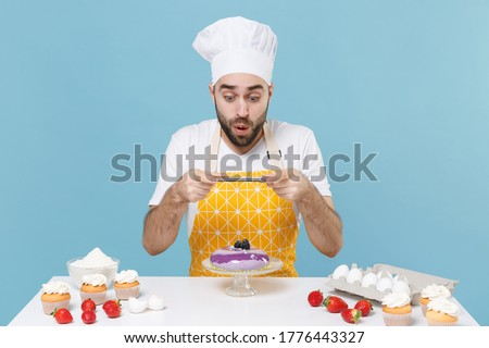 Shocked young male chef or cook baker man in apron white t-shirt toque chefs hat cooking at table isolated on blue background. Cooking food concept. Taking pictures of dessert cake on mobile phone