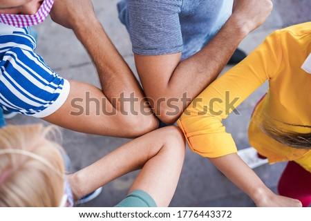 Young people friends bump their elbows instead of greeting with a hug - Avoid the spread of coronavirus, social distance and friendship concept  Royalty-Free Stock Photo #1776443372