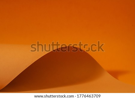 Orange and brown paper is curved by a wavy line, beautiful soft light and shadow on paper, abstract background for designers. Royalty-Free Stock Photo #1776463709