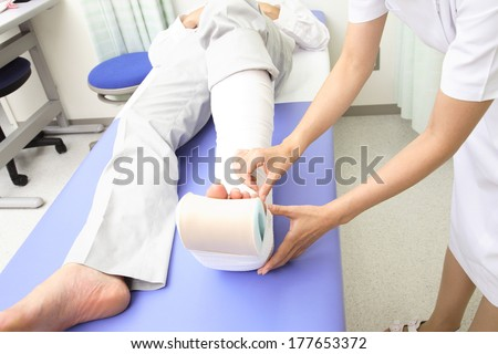 Japanese Nurse putting the bandage on the foot of the patient #177653372