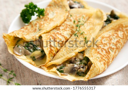 Savory Homemade Mushroom, Spinach and Cheese Crepes on a white plate, side view. Close-up. Royalty-Free Stock Photo #1776555317
