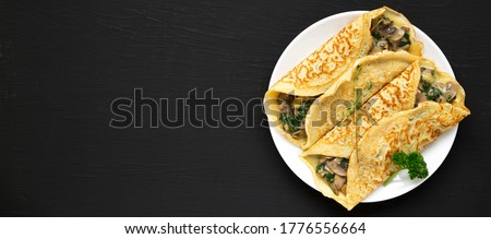 Savory Homemade Mushroom, Spinach and Cheese Crepes on a white plate on a black background, top view. Flat lay, overhead, from above. Space for text. Royalty-Free Stock Photo #1776556664
