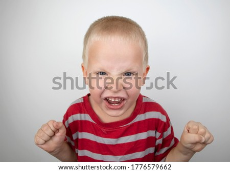 Angry boy screaming and hysteria on a white background. Four-year-old child shows child aggression Royalty-Free Stock Photo #1776579662