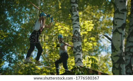 Man and woman crossing the rope bridge - an entertainment attraction in the green forest Royalty-Free Stock Photo #1776580367