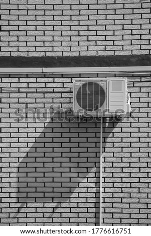 Black and white photo of a air conditioner fan box on the outside of a building