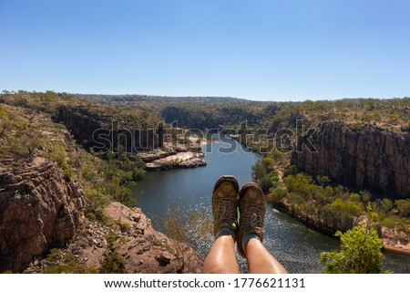 Hiking boots and legs above river and canyon. Woman hiking at Katherine gorge. Aerial view. Katherine gorge, Nitmiluk national park, Northern Territory NT, Australia