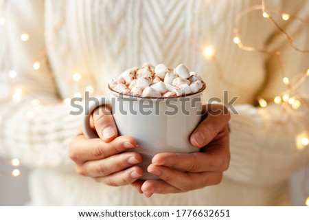 Young girl in knitted white wool sweater is holding a mug with hot chocolate or coffee with marshmallow. Christmas lights on, cozy holiday atmosphere, aromatherapy for cold winter season. Closeup #1776632651