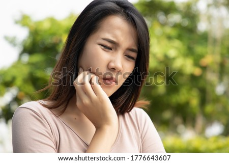 woman with toothache; sick asian woman suffering from toothache, tooth decay, tooth sensitivity, wisdom tooth pain, cavity, dental care concept; young adult asian woman model Royalty-Free Stock Photo #1776643607