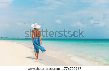 Caribbean beach vacation luxury elegant lady walking in blue beach wrap sarong skirt relaxing on idyllic holiday white sand beach stroll. #1776700967