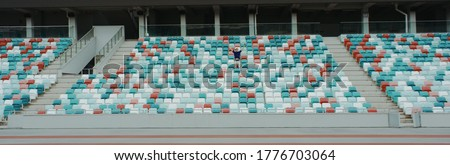 WIDE view of a lonely fan spectator attending a sports event on an empty stadium. Isolation, events during coronavirus pandemic concept Royalty-Free Stock Photo #1776703064