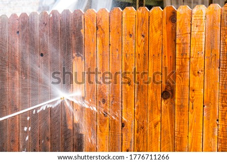 Stay at Home house repairs , Pressure Washing Fence with a high pressure washer , cleaning old dirty planks of wood on Wooden Fence in Suburb Neighborhood Royalty-Free Stock Photo #1776711266