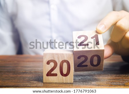 Hand flips a block changing 2020 to 2021. New year beginning. Holidays and Christmas. Trends and changes in the World. Build plans. New normal. Summing work done. Keep up with everything planned. #1776791063