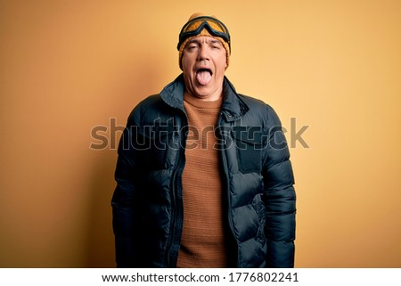 Middle age handsome grey-haired skier man on vacation wearing ski goggles sticking tongue out happy with funny expression. Emotion concept. #1776802241