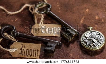 two old keys on a rusty metal table with labels : escape room #1776811793