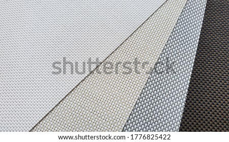 close up roller blind curtain samples. interior textile fabric palette catalog in various color.  Royalty-Free Stock Photo #1776825422