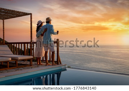A romantic couple on summer vacation enjos the sunset over the mediterranean sea by the pool with a glass of Aperitif Royalty-Free Stock Photo #1776843140