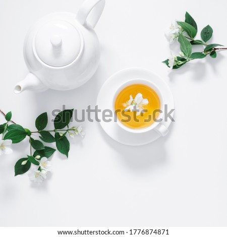Jasmine flowers and teapot on white background. Herbal tea of jasmine flower. Jasmine tea concept. Flat lay, top view, copy space #1776874871
