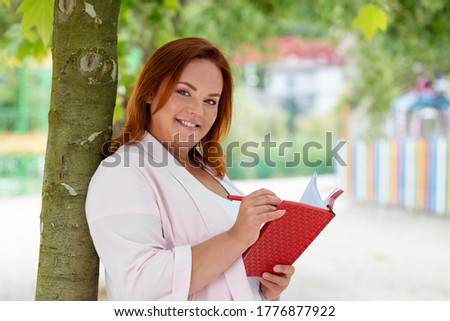 Freelance. Portrait of a Caucasian smiling woman holding a notebook and writing something in it. Plus size model. Outdoor. Concept of remote work and education
