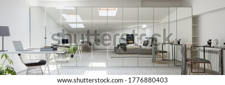 Panorama of stylish attic bedroom with gray bed, desk, ceiling windows and white walls and large wardrobe with mirror doors Royalty-Free Stock Photo #1776880403