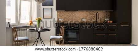 Panorama of stylish kitchen with black furniture and copper hexagonal wall tiles with black, dining table and two copper chairs #1776880409