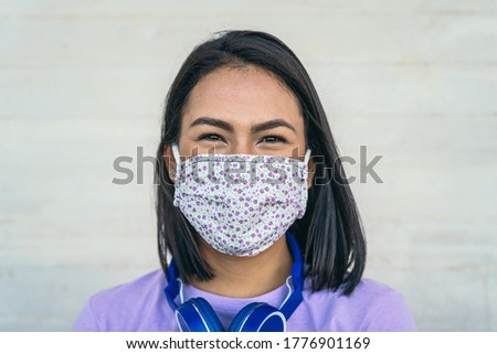 Young woman wearing face mask portrait - Latin girl using protective facemask for preventing spread of corona virus - Health care and pandemic crisis concept  Royalty-Free Stock Photo #1776901169